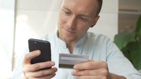 Compras del hombre joven con una tarjeta de crédito en una mano y un smartphone en la otra almacen de metraje de vídeo