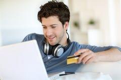 Compras del hombre joven en Internet Fotografía de archivo libre de regalías
