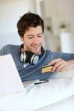 Compras del hombre joven en Internet Imagen de archivo