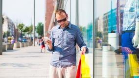 Compras del hombre joven en la alameda con muchos bolsos de compras coloreados en su mano. Él está sosteniendo un teléfono. Fotos de archivo libres de regalías