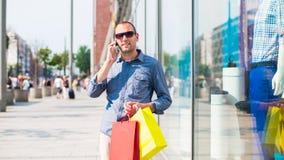 Compras del hombre joven en la alameda con muchos bolsos de compras coloreados en su mano. Él está sosteniendo un teléfono. Fotos de archivo