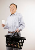 Compras del hombre para las tiendas de comestibles con la lista de compras Fotos de archivo libres de regalías
