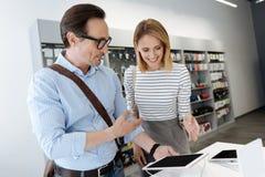 Compras del hombre y de la mujer para la tableta en la tienda Imagen de archivo libre de regalías