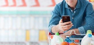 Compras del hombre y usar apps móviles imagenes de archivo