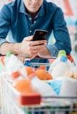 Compras del hombre y usar apps móviles imagen de archivo libre de regalías