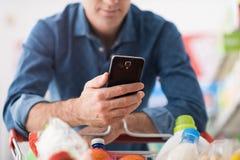 Compras del hombre y usar apps móviles fotos de archivo libres de regalías