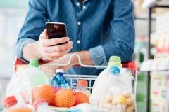Compras del hombre y usar apps móviles fotografía de archivo libre de regalías