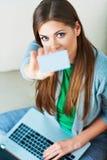 Compras del ordenador portátil de la mujer con la tarjeta de crédito Imagen de archivo libre de regalías