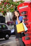 Compras del smartphone de la mujer de Londres que hablan Imágenes de archivo libres de regalías