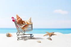 Compras del verano Negocio y venta en la playa Carro en la arena blanca imagen de archivo