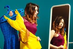 Compras del vestido de la mujer que intentan para la ropa Foto de archivo libre de regalías
