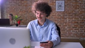 Compras divertidas felices del oficinista a través de Internet en el ordenador portátil y usar su tarjeta de crédito, hombre aleg metrajes