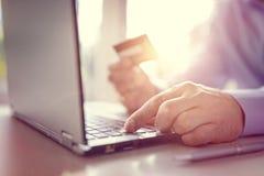 Compras en línea con la tarjeta y el ordenador portátil de crédito fotos de archivo libres de regalías