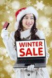 Compras en línea de la muchacha con la tarjeta de crédito en venta del invierno Imagen de archivo libre de regalías