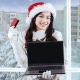 Compras en línea de la mujer joven para Navidad Imagenes de archivo