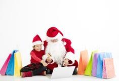 compras en línea de la Navidad de Papá Noel y del niño fotografía de archivo