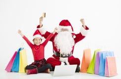 compras en línea de la Navidad de Papá Noel y del niño foto de archivo libre de regalías