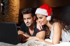 Compras en línea de los pares jovenes felices para la Navidad Foto de archivo libre de regalías