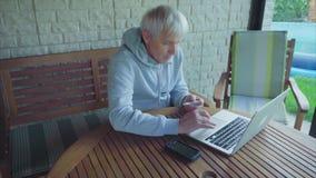 Compras en línea del hombre mayor con la información de la tarjeta de crédito del ordenador portátil que entra almacen de metraje de vídeo