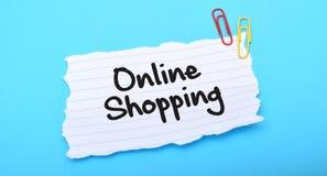 Compras en línea escritas en el papel con el fondo azul fotografía de archivo libre de regalías