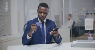 Compras en línea Hombre joven negro en traje usando tarjeta de crédito almacen de video