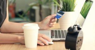 Compras en línea Manos caucásicas jovenes que compran mercancías de Internet en su smartphone con su tarjeta de crédito