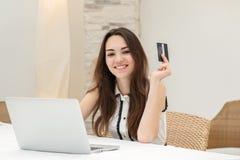 Compras en línea Muchacha joven y bonita que se sienta en un ordenador portátil y un m Imagenes de archivo