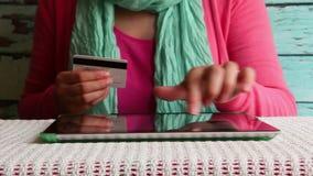 Compras en línea, mujer con la tarjeta de crédito a disposición que paga o que reserva en Internet almacen de video