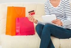 Compras en línea mujer joven sonriente con la tableta y la tarjeta de crédito Fotografía de archivo
