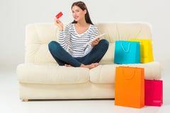 Compras en línea mujer joven sonriente con la tableta y la tarjeta de crédito Foto de archivo libre de regalías