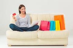 Compras en línea mujer joven sonriente con la tableta y la tarjeta de crédito Imagenes de archivo