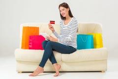 Compras en línea mujer joven sonriente con la tableta y la tarjeta de crédito Fotos de archivo libres de regalías
