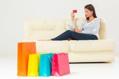 Compras en línea mujer joven sonriente con la tableta y la tarjeta de crédito Imágenes de archivo libres de regalías