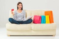 Compras en línea mujer joven sonriente con la tableta y la tarjeta de crédito Imagen de archivo libre de regalías
