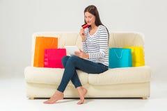 Compras en línea mujer joven sonriente con la tableta y la tarjeta de crédito Fotos de archivo