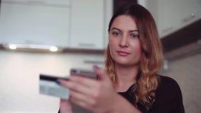 Compras en línea Una chica joven hermosa incorpora su información de la tarjeta de crédito en un smartphone para hacer una compra almacen de video