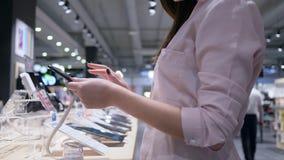 Compras en la sala de exposición de la tienda de los productos electrónicos de consumo, comprador que usa una nueva tableta moder almacen de metraje de vídeo