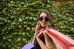 Compras Feche acima do retrato da menina caucasiano bronzeado-descascada atrativa nova nos óculos de sol e no vestido preto que g imagem de stock royalty free