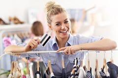 Compras felices de la mujer para la ropa con la tarjeta de crédito fotografía de archivo libre de regalías