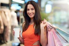Compras felices de la mujer para la ropa en tienda foto de archivo libre de regalías