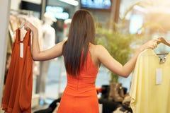Compras felices de la mujer para la ropa en tienda fotografía de archivo libre de regalías
