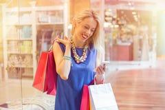 Compras felices de la mujer y usar el teléfono móvil Fotografía de archivo libre de regalías
