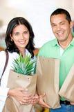 Compras felices de los pares en supermercado con los bolsos Fotos de archivo libres de regalías
