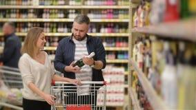 Compras felices de los pares en supermercado Familia joven que elige el vino de estantes del supermercado almacen de metraje de vídeo