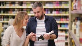 Compras felices de los pares en supermercado Familia joven que elige el vino de estantes del supermercado almacen de video