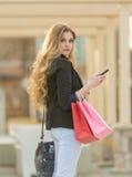 Compras femeninas rubias jovenes con los bolsos rosados y rojos que sostienen un teléfono celular Imagen de archivo libre de regalías