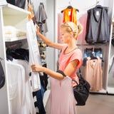 Compras hermosas de la mujer en tienda de ropa Fotografía de archivo