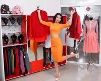 Compras hermosas de la mujer joven en una tienda de ropa fotografía de archivo libre de regalías