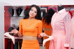 Compras hermosas de la mujer joven en una tienda de ropa foto de archivo libre de regalías