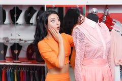 Compras hermosas de la mujer joven en una tienda de ropa imagenes de archivo
